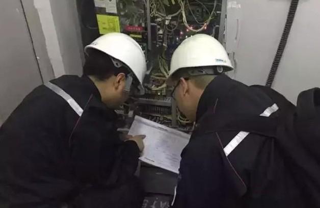 成都电梯维修的师徒二人正在研究电梯供电电路